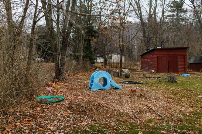 A blue plastic slide, shaped like an elephant with a curling trunk, sits unused in the leaf-strewn yard of the house in the 1000 block of North River Road in Halifax Township.