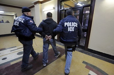 Immigration and Customs Enforcement officers escort an arrestee in an apartment building, in the Bronx borough of New York, during a series of early-morning raids in 2015. (AP Photo/Richard Drew, File)