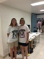 """Jenny Blom, left, and Linda Farr, part of the Concerned Citizens of Lemoyne Middle School Project, stand in front of their table of """"Save Our School"""" T-shirts on Wednesday night."""