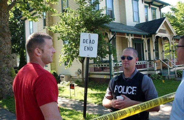 Sunbury Police Chief Timothy S. Miller, left, speaks with a Milton officer outside the duplex in the 700 block of North Front Street of that borough where investigators are searching for the body of Barbara E. Miller who was last seen in 1989. Miller announced he is leaving his job with the borough to become a barber and said Tuesday he is disappointed that he won't be able to carry the cold case investigation to a conclusion.