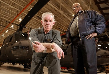 Army pilot John Travers (left) and Navy medic Ray Thorn stand in front of Vitnam era Bell Huey helicopters in the hangar at Fort Indiantown Gap. Friday, Feb. 6, 2004.