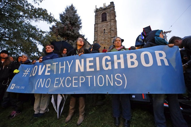 A group holds a sign at the intersection of Murray Ave. and Forbes Ave. in the Squirrel Hill section of Pittsburgh, during a memorial vigil for the victims of the shooting at the Tree of Life Synagogue where a shooter opened fire, killing multiple people and wounding others, including several police officers, Saturday, Oct. 27, 2018.