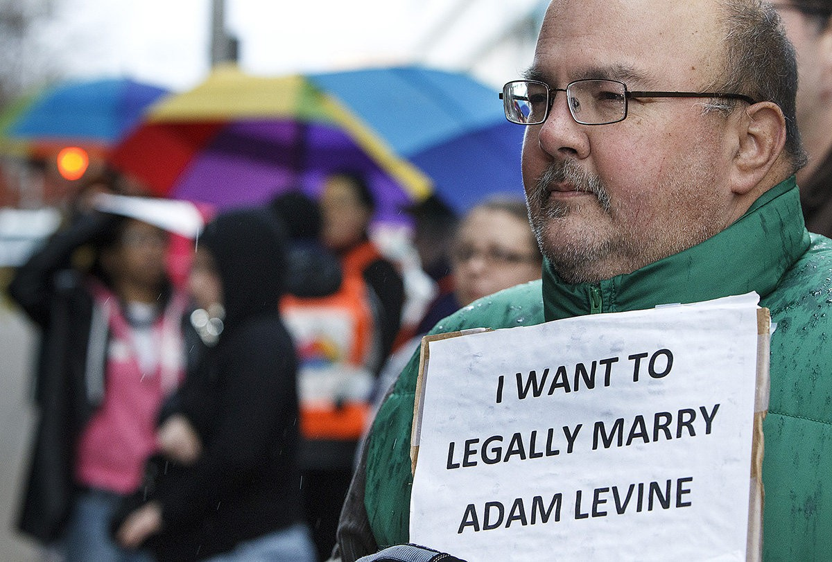 A marriage equality rally takes place in front of the federal courthouse in Harrisburg in March 2013. Michael Escobar, of Elizabethtown, takes part in the rally.