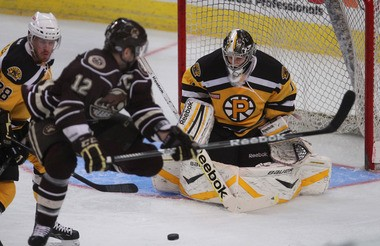 Providence Bruins goalie Niklas Svedberg stops a shot in the second period as Kevan Miller, left, and Hershey's Boyd Kane follow the action. (The Providence Journal/Glenn Osmundson)