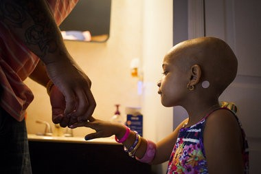 After scraping her finger, Leah Still bites her lip as her father, Cincinnati Bengals defensive tackle Devon Still, applies a Band-Aid on July 13, 2014.