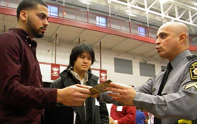 State Police Cpl. Daniel Gonzalez speaks with Brandon Hernandez, 20, and Wyman Vien, 23, at a career fair at Thaddeus Stevens College of Technology in Lancaster.