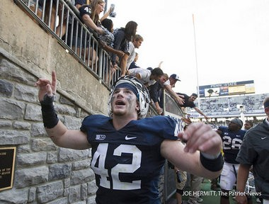 Penn State linebacker Michael Mauti celebrates with students after the 34-7 win over Navy giving Bill O'Brien his first victory as head coach.