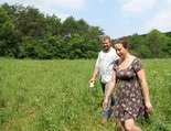 FARMING THE DOUGH -- Joe Amsterdam and Shana Slossberg walk the fields on their Carroll Twp. farm. The couple hope agri-tourism efforts in the county bring more business and visitors.