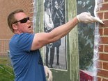 HITTING THE WALL -- Artist Jonathan Laidacker is working with Greenwood High School students on a mural for the Millerstown firehouse.