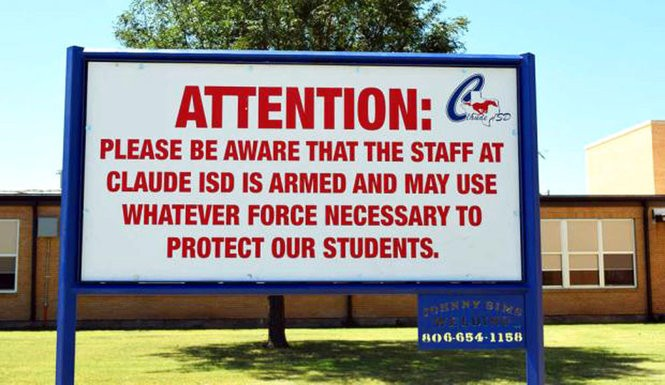"""This August 2016 photo shows a sign outside a school in Claude, Texas, which Claude ISD posts outside their schools. In the aftermath of yet another mass school shooting, President Donald Trump says that if one of the victims, a football coach, had been armed """"he would have shot and that would have been the end of it."""" Revisiting an idea he raised in his campaign, Trump's comments in favor of allowing teachers to be armed come as lawmakers in several states are wrestling with the idea."""