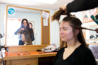 Priscilla Mateo, seen here working on Megan Walgren while a student at the Lancaster School of Cosmetology, has since graduated and now is left waiting for her state cosmetology license to arrive so she can begin earning a paycheck cutting hair.