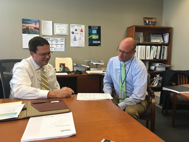 PHEAA's interim president and CEO James Steeley (left) looks over a report with senior vice president Nathan Hench.