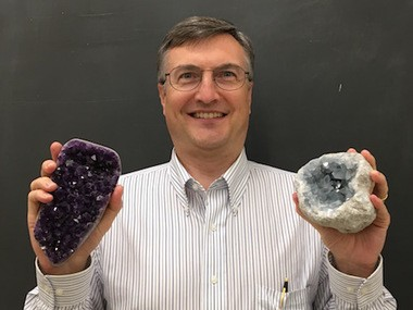 Penn State minerology professor Peter Heaney displays amethyst in his left hand and celestine in his right. Both are minerals that state lawmakers want to make state symbols.