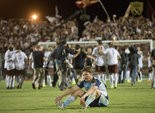 Dejected City Islanders forward Antoine Hoppenot sits in the middle of Bonney Field following Harrisburg's 2-1 loss to the Sacramento Republic in Saturday's USL PRO championship game. In the background, Sacramento players celebrate the league championship.