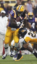 LSU running back Spencer Ware (11) , who is now with the Kansas City Chiefs, is hit by Bryton Barr (22) during a game in the 2012 season.