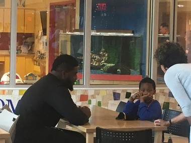 Steelers offensive tackle Chukwuma Okorafor visits with a child and his mother at UPMC Children's Hospital in Lawrenceville on Monday.