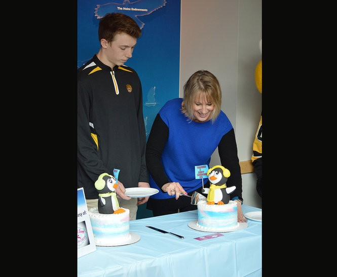 Jane Dixon, a member of the board of directors at the National Aviary in Pittsburgh, cuts into a a specially designed cake to reveal the gender of one of the two African penguin chicks.