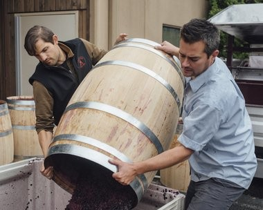 Washington state winemakers Graham Whye, left, and Morgan Lee dump a barrel. The two have worked together since 2013.