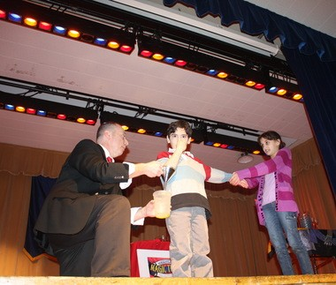 """Magic Mike"" Sherman performs some hocus-pocus with the aid of students Nicholas Storniolo and Gianna Baratta at a fundraiser for PS 53 in Bay Terrace."