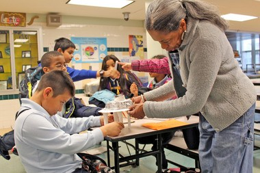 Sajda Musawwire Ladner, artistic and executive director of Universal Temple of the Arts, helps Alejandro Juanet with his art project made from recycled materials, during a workshop at PS 65 in Stapleton.