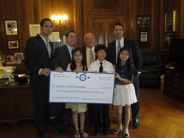 Borough President James Molinaro and three youngsters from PS 69, present a check to the non-profit group ConstructRELIEF, for Hurricane Sandy repairs. The youngsters are, from the left, Josephine Man, Joseph Lee and Belinda Zhang.