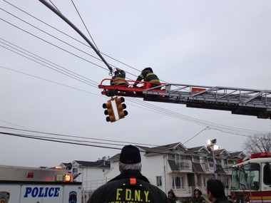 Responders work to secure a traffic light that was loosened in the crash.