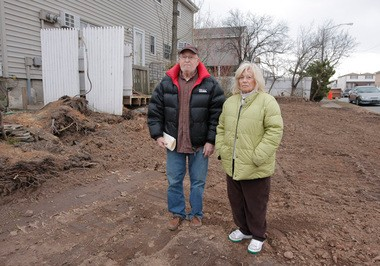 """Mark and Carol Meyer stand on the tiny lot next to their home at Haven and Adams avenues in Midland Beach. Mrs. Meyer maintained a garden on the site for more than 40 years. """"I made it beautiful,"""" she said."""