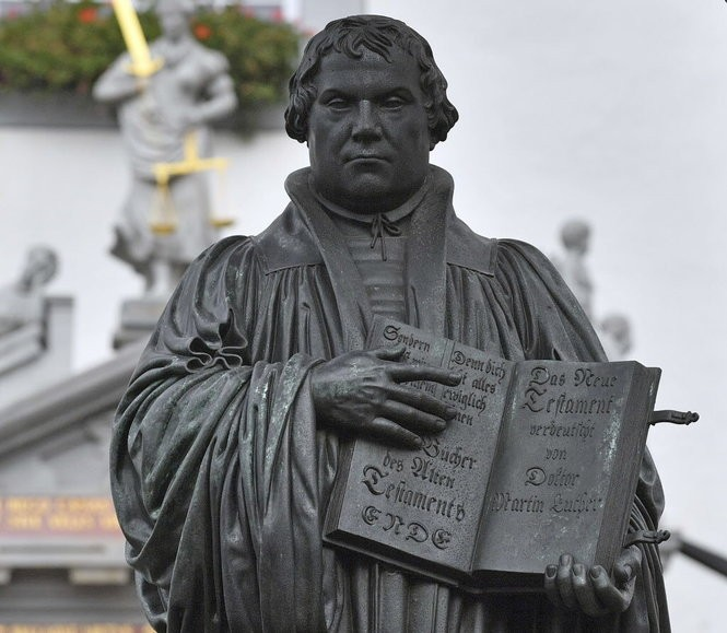 The Martin Luther memorial can be seen on the market square in Wittenberg, Germany, Tuesday, Oct. 31, 2017. German leaders will mark the 500th anniversary of the day Martin Luther is said to have nailed his theses challenging the Catholic Church's practice of selling indulgences to a church door, a starting point of the Reformation. (Hendrik Schmidt/dpa via AP)