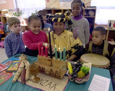 CIRCA 2000: Janet G. Robinson, center, is surrounded by students from the Michael J. Petrides School in Sunnyside, as she explains the meaning and symbols of Kwanzaa, which begins today. Joining her are, from left, Matthew Hinkley, Kenisha Jones, James Silverence, Comfort Gwelekai and Tristan Wilds. Mrs. Robinson, of Stapleton, is known as the 'Kwanzaa Lady' for her annual presentations at Staten Island schools, day care centers and senior centers.