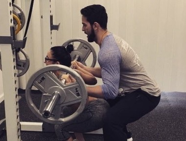 Matt Geib, of Transformation Fitness in Graniteville, assists his client, Gabriella Cohen, with squats.