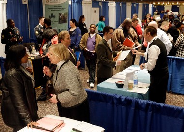 Job-seekers and business representatives talk during the a career fair at the Empire State Plaza Convention Center in Albany on April 11.