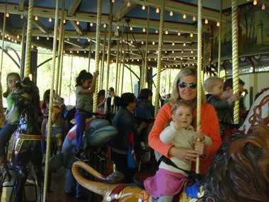 Elizabeth Pilacinsai of Oakwood waves while riding on the Carousel for All Children with her mother, Margaret. The delightful childrenas attraction in Willowbrook Park opened for the season Saturday.