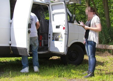 An inspector takes notes while a contractor gathers belongings prior to the seizure of his van. Due to the undercover nature of the inspectors' work, we are shielding their identities in this report.