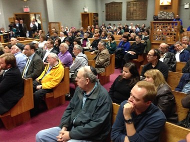 Crowd listens attentively during meeting in temple.