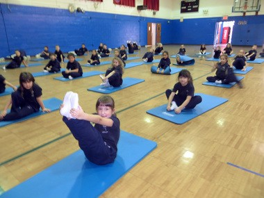 Abigail Memmesheimer, foreground, a student at Our Lady Queen of Peace School, New Dorp, warms up with a stretch before her Pilates class in the school gym.