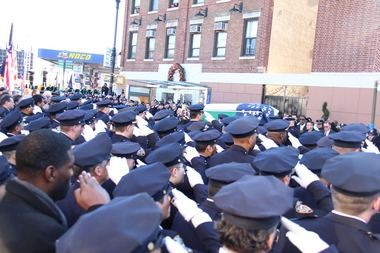 Police stand in attention as slain Officer Rafael Ramos' casket leaves Christ Tabernacle Church during the Glendale, Queens, funeral. (Staten Island Advance/Vincent Barone)