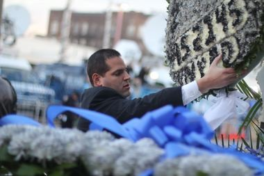 Members of the NYPD assemble slain Officer Ramo's flower car before the funeral service on Saturday at Christ Tabernacle Church in Glendale, Queens. (Staten Island Advance/Vincent Barone)