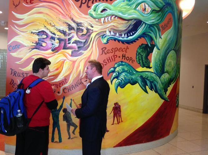 Sophomore Ronald Boylan listens as Principal Joseph Canale explains how the dragon mural was created by students for the CSI High School main lobby. As the school mascot, a dragon serves as a link to the Asia Society. (Staten Island Advance/Claire Regan)