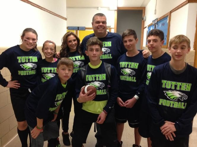 Just off the field and dressed in their Totten Football jerseys, students join Principal John Boyle for a group shot. (Staten Island Advance/Claire Regan)