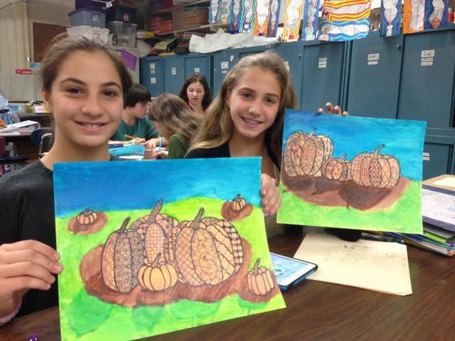 Totten Intermediate seventh-graders Angelina Montemorano and Ava Patti display their pumpkin artwork. (Staten Island Advance/Claire Regan)