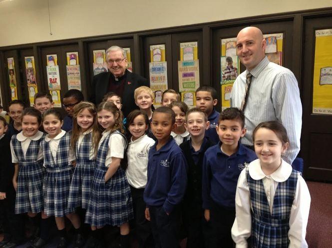 Monsignor Peter Finn and Principal Joseph Cocozello join second-graders in their classroom. (Staten Island Advance/Claire Regan)