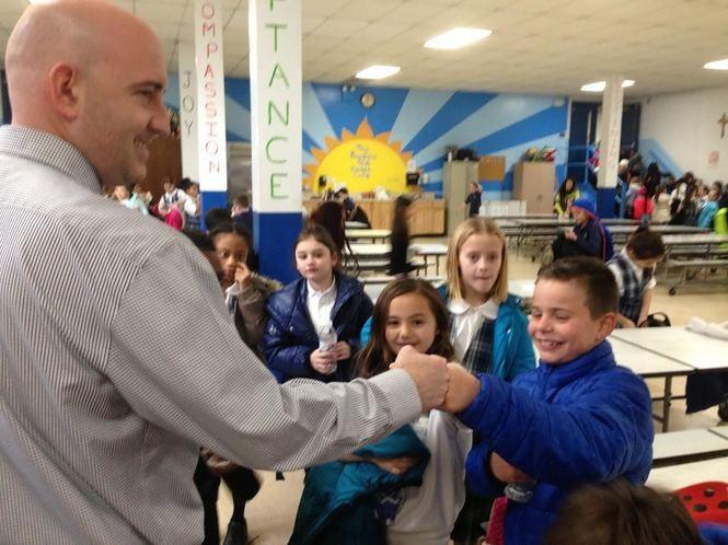 Third-grader Lucas Grigos greets Principal Joseph Cocozello with a fist bump in the Blessed Sacrament cafeteria. (Staten Island Advance/Claire Regan)