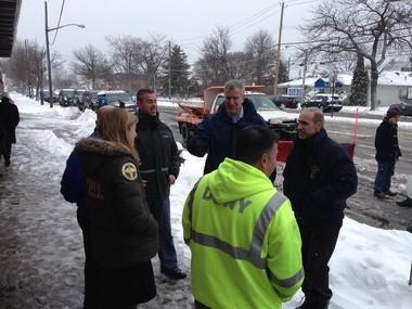 Mayor Bill de Blasio and Borough President James Oddo walk along Hylan Boulevard in Ocean Breeze, speaking with Sanitation workers.