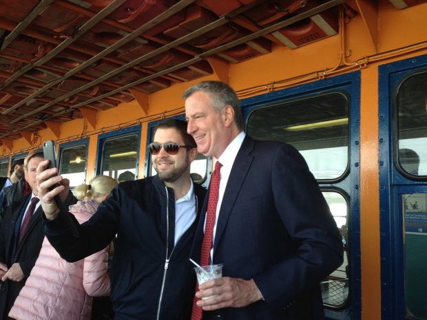 Mayor Bill de Blasio poses for a photo with a tourist from Stockholm as he travels to Staten Island via ferry. Monday, April 10, 2017.