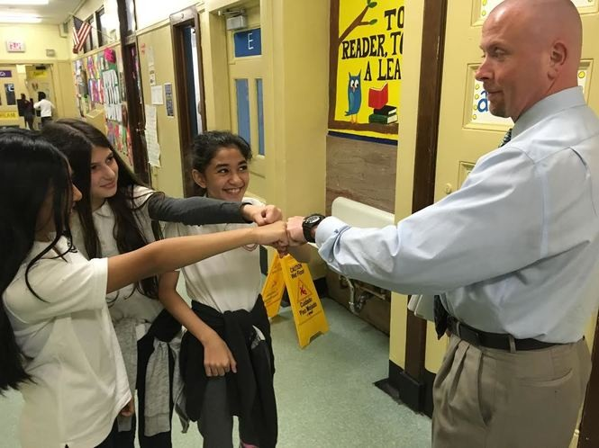 Second-grade teacher Anthony Musachio gives his former students a fist bump. From the left are fifth-graders Jayleen Garcia, Ema Chaka and Leila Saeed. (Staten Island Advance/Claire Regan)