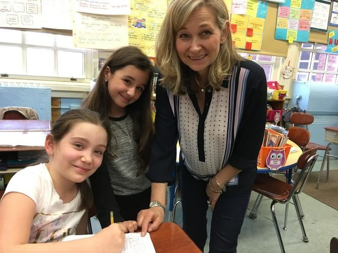 Sophie Yarkhunov and Sonila Osmani get some assistance from their fourth-grade teacher, Renata Kozyra. (Staten Island Advance/Claire Regan)