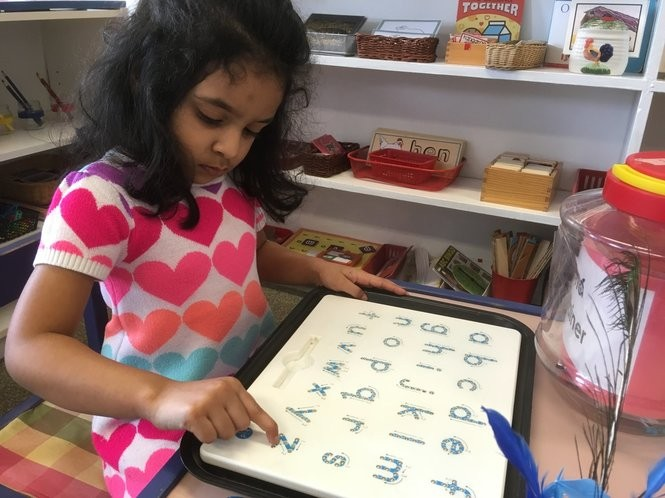 Nicolina Thebuwanage traces letters of the alphabet. (Staten Island Advance/Claire Regan)
