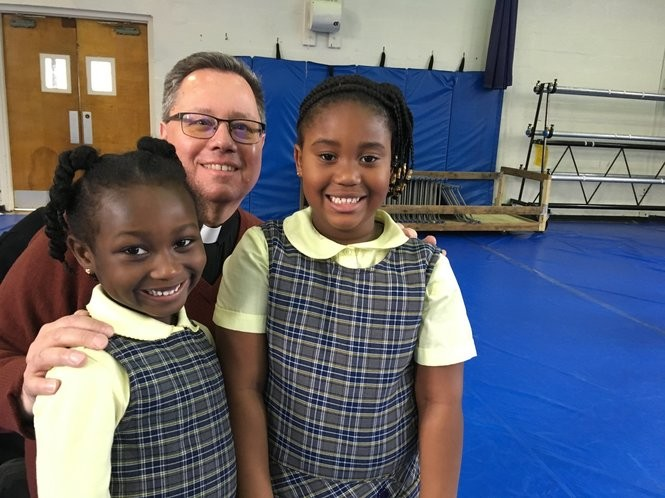 Kindergartners Madysen Kwaafo, left, and Edlinda Brosius visit with the Rev. Michael Cichon in the St. Peter-St. Paul School gym. (Staten Island Advance/Claire Regan)