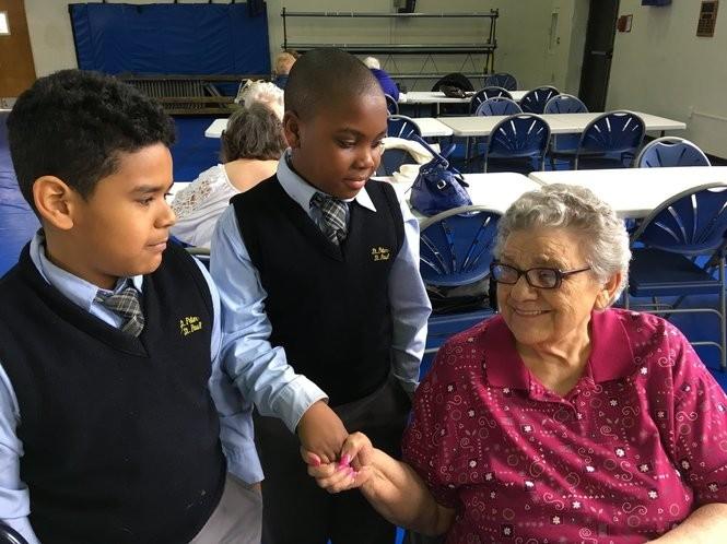 Third-graders Ethan Salas and Anthony Chester greet Mathilda Presutti, a member of the Assumption Seniors. (Staten Island Advance/Claire Regan)