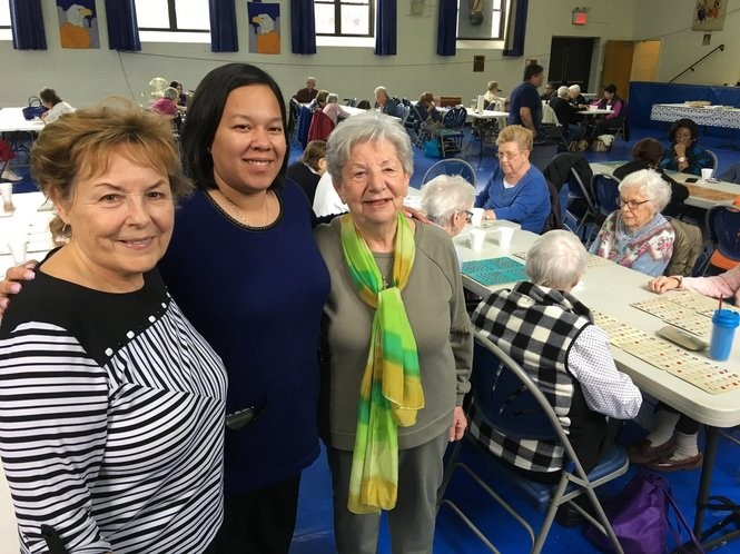 St. Peter-St. Paul Principal Jennifer Olivera, center, visits with Assumption Seniors Marge Dellacato, left, and Carmella Ruggiero at the group's weekly bingo game in the school gym. (Staten Island Advance/Claire Regan)